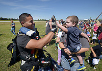 NWA Democrat-Gazette/BEN GOFF @NWABENGOFF<br /> Konnor Bowman (CQ), 2, of Pineville, Mo., high-fives Dozer Hernandez from Skydive Skyranch in Siloam Springs after his jump on Saturday Sept. 12, 2015 during the Sheep Dog Impact Assistance annual Patriot Day event at Bentonville Municipal Airport. The event honored the victims of the Sept. 11, 2001 terrorist attacks and offered visitors a chance to get an up close look at military and emergency response vehicles.