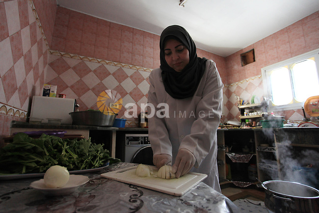 "A Palestinian woman Dalal al-Bardawil, 53, prepares ""Samaqia"", traditional meal of Gazans, to sell it for customers, at her own kitchen in Gaza city on March 14, 2018. Samaqia consists of ""meat, onions, flour, spices, olive oil, cicla, sumach and Red tahini"". Palestinians in Gaza strip deliver Samaqia dishes in weddings and holidays. Photo by Mahmoud Ajour"