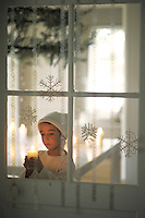 A boy dressed in white gazes at the candle he is holding and is framed by sparkling snowflake decorations