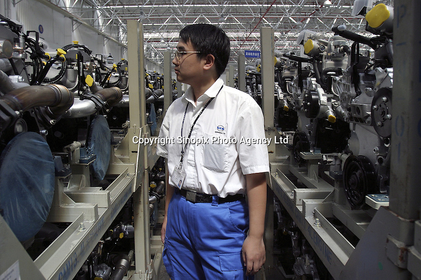 A Chinese General Motors employee makes a final inspection on engines about to be shipped to Canada at the Shanghai General Motors plant in Shanghai, China. The engines will be assembled on the GM model Equinox, which is a vehicle made of parts from around the world, very few of which are actually made in the USA..