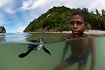 Leatherback sea turtle (Dermochelys coriacea) with West Papuan kids in the water