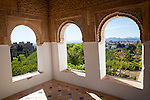 Arched decorated Moorish stone windows looking over gardens, Generalife garden, Alhambra, Granada, Spain