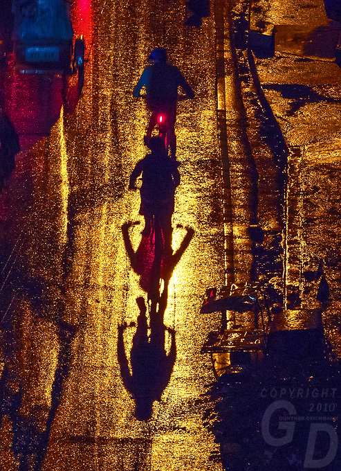 Push Bike riders during the Monsoon season in Manila, dramatic light and a heavy rain shower at night viewed from above made for some abstract images.