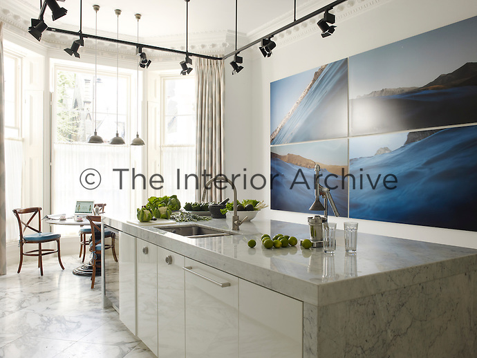 The contemporary kitchen is lit by runway-style lights and is decorated with photographs by Montserrat Soto
