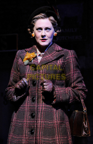 "SARAH LANCASHIRE .On stage during the ""Betty Blue Eyes"" photocall, Novello Theatre, London, England, UK, April 4th 2011..half length actress costume musical gloves plaid checked coat  red brown leather flower corsage brooch scene .CAP/CAN.©Can Nguyen/Capital Pictures."