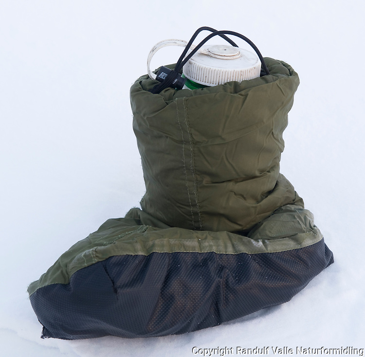 Drikkeflaske holdes varm i bivuakksko. ---- Bottle in insulating shoe.