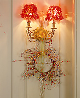 A sconce with red beaded shades is decorated with a festive wreath tied with ribbon