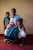 31 years old Suthakaran Shanthirakala poses for  photo with her children and the CHDR- Child Health Development Record Card (immunization/vaccination card) in Punaineeravi Village in Kilonochchi, Sri Lanka.  Photo: Sanjit Das/Panos