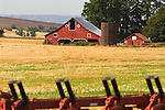 Plow in field, red barn with silo, harvested grain field, oaks; windfarm on distant hills in southern Washington state.