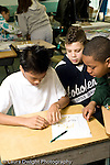 Education Elementary school Grade 5 class with science specialist making models from toothpicks and mini marshmallows 3 male students working together vertical
