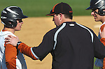 A Jersey Shore High School coach talks with two base runners during a break in action.