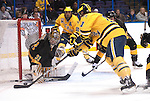 March 26,  2011                      Michigan forward Kevin Lynch (11) tries to push the puck past Colorado goalie Joe Howe (31) in the first period. The University of Michigan was leading Colorado College 2-0 after the first period in the championship game of the NCAA Division 1 Men's West Regional Hockey Tournament, on Saturday March 26, 2011 at the Scottrade Center in downtown St. Louis.
