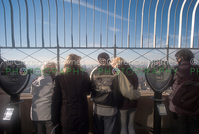 Tourists enjoy the view of New York City from the observation deck of the Empire State Building.