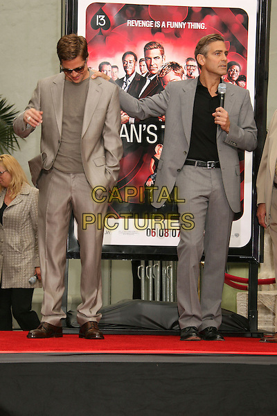 "BRAD PITT & GEORGE CLOONEY .""Ocean's Thirteen"" Handprint and Footprint Ceremony held  at Grauman's Chinese Theatre, Hollywood, California, USA..June 5th, 2007.full length beige suit jacket hands in pockets sunglasses shades grey gray microphone speech hand on shoulder .CAP/ADM/RE.©Russ Elliot/AdMedia/Capital Pictures"