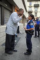 Switzerland. Geneva. Paquis neighborhood. A short police officer talks to a tall drunk man. 7.07.12 © 2012 Didier Ruef..