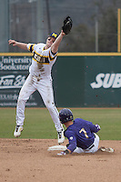 Michigan Wolverines shortstop Travis Maezes (9) leaps for the throw as Washington Huskies baserunner Braden Bishop (7) slides safely into second base during the NCAA baseball game on February 16, 2014 at Bobcat Ballpark in San Marcos, Texas. The game went eight innings, before travel curfew ended the contest in a 7-7 tie. (Andrew Woolley/Four Seam Images)