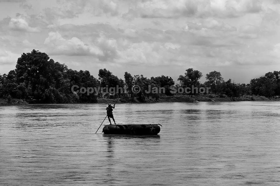 A makeshift inner tube raft, used for smuggling people and goods, crosses the Suchiate river from Mexico to Tecún Umán, Guatemala, 22 May 2011. Having no migration or commercial controls, the Suchiate river serves as an illegal crossing point between the southern Mexican state of Chiapas and Guatemala. Every day, hundreds of people from both countries, crossing the river on the unstable rafts called ?camaras?, smuggle soft drinks, toilet papers, fruits, vegetables and other supplies. The river crossing is also widely used by the Central America immigrants heading to the north, to the United States, in the search of better life.