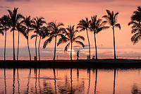 A man strolls past an orange sunset and palm trees at Waikoloa, Big Island.