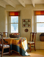 A 19th century Amish quilt is used as a tablecloth, a fragment of a baby quilt is used to cover a chair and a panel from a sampler hangs upon the wall of this dining room