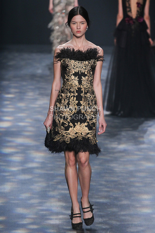Model Isis walks runway in a black statin strapless cocktail with antique gold floral and tassel threadwork embroidery with ostrich feather trim, from the Marchesa Fall 2016 collection by Georgina Chapman and Keren Craig, presented at NYFW: The Shows Fall 2016, during New York Fashion Week Fall 2016.