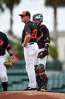 GCL Orioles manager Matt Merullo (27) makes a pitching change as Stuart Levy (15) looks on during the second game of a doubleheader against the GCL Rays on August 1, 2015 at the Ed Smith Stadium in Sarasota, Florida.  GCL Orioles defeated the GCL Rays 11-4.  (Mike Janes/Four Seam Images)