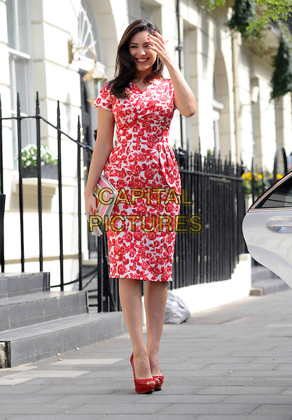 Kelly Brook.Spotted in London, England..April 24th, 2013.full length red white floral print dress peep toe platform shoes clutch bag pink yellow peplum hand arm  waving.CAP/AOU.©AOU/Capital Pictures.