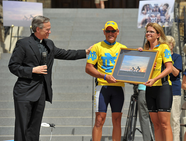 "University president Rev. John Jenkins, C.S.C. presents a photo to College of Science Dean Greg Crawford and his wife Renate during a ceremony welcoming them back to campus after their ""Desert to Dome"" bike ride from Tucson, AZ to South Bend, IN to promote the Notre Dame-Parseghian Foundation partnership...Photo by Matt Cashore/University of Notre Dame"