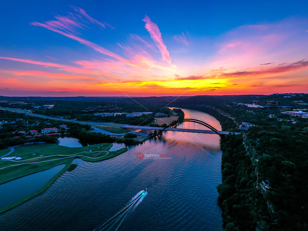 While flying my drone at the 360 Bridge in Austin, Texas I found this amazing fiery sunset that evening. This is the most spectacular sunset I've come across in years. This panorama looks west along Lake Austin, the Colorado river. The 360 Bride is Austin's most famous iconic Bridge (officially named Pennybacker Bridge). In the foreground, a ski boat speeds along Lake Austin with a cool green LED light illuminating the stern of the boat and water stream behind it.