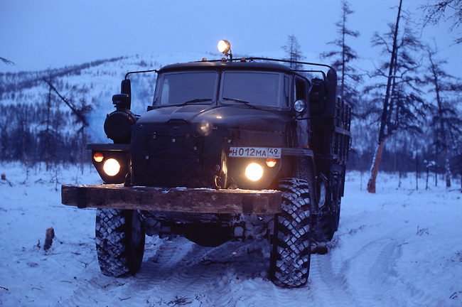 An Ural truck carrying supplies on a winter road in taiga at dusk. Northern Evensk, Magadan Region, E. Siberia, Russia