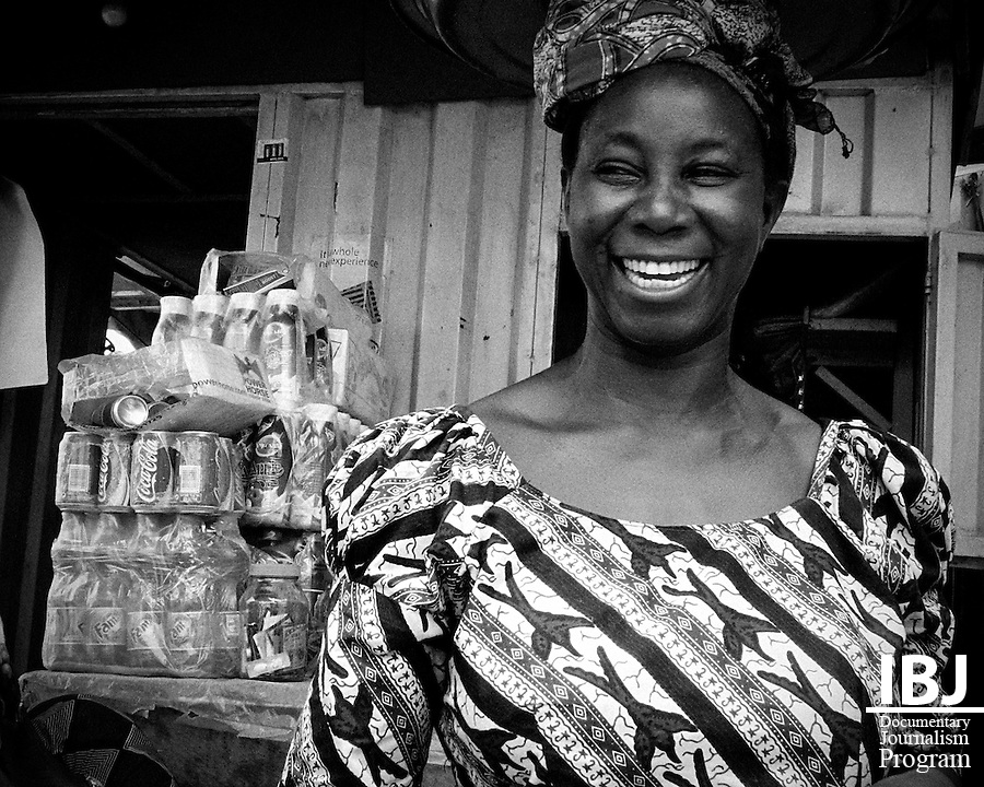 Woman smiles while tending her shop in Ojota, Lagos Nigeria. As a result of extremely high unemployment rates much of the local economies are a result of markets and roadside shops.