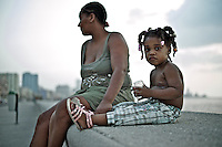Images from the old Havana, Cuba, Latin America. ..Girl in the malecon at sunset.