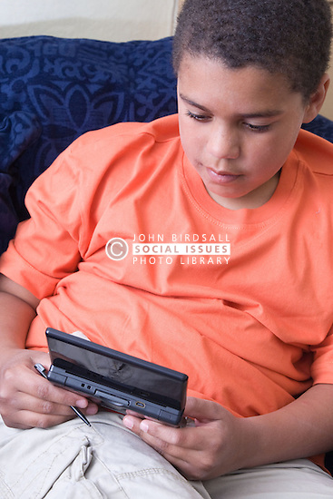 Young boy playing a computer game on a hand held consul,