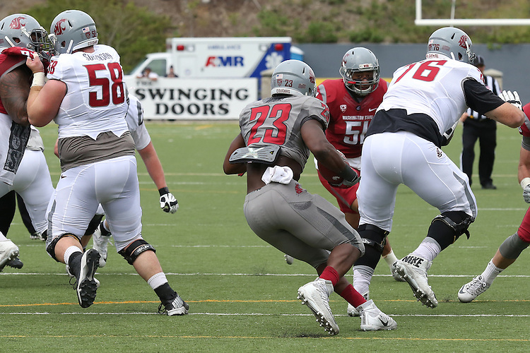 Gerard Wicks (23) finds a crease between blocks by Riley Sorenson (58) and Cody O'Connell (76) during the annual Washington State Cougar spring game, the Crimson and Gray game, at Joe Albi Stadium in Spokane, Washington, on April 23, 2016.