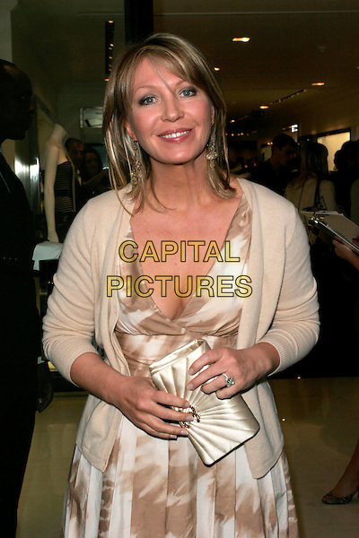 KIRSTY YOUNG.Flagship store launch party, Michael Kors boutique, London, England. .April 27th, 2009 .half length gold beige white cream dress clutch bag cardigan cleavage .CAP/AH.©Adam Houghton/Capital Pictures.