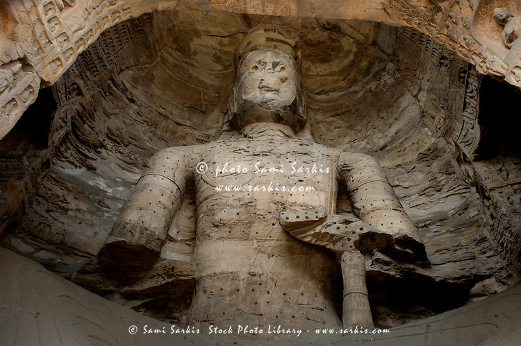 Damaged Buddha statue carved inside the ancient Yungang Grottoes, Datong, Shanxi, China.