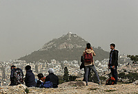 Pictured: People enjoy the view towards Lycabetus Hill in Athens Greece. Monday 26 March 2018<br /> Re: Strong southern winds from Africa have carried red dust over to Greece.
