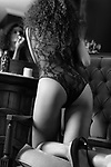 Artistic sensual black and white portrait of a young woman in sexy lacy underwear standing on her knees in a chair leaning onto a dresser applying lipstick looking in the mirror. French retro style boudoir.