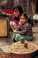 Two young sisters sit on steps beside mother's basket of peanuts for sale; both smile; 3 4 left view. Kathmandu, Nepal.
