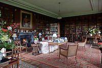 Antique leather-bound books line the walls of this impressive library which is furnished with comfortable seating