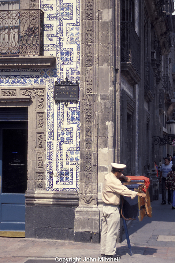 Organ grinder outside the Casa de los Azulejos or House of Tiles in dpwntown Mexico City. This colonial building houses Sanborns department store and restaurant.