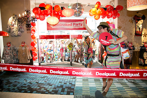 "Tokyo, Japan - The first customer enters the Desigual store in Tokyo's Harajuku fashion district. A fashion chain called ""Seminaked Party by Desigual"" offers the first 100 customers (wearing swimsuit) free clothing items at the grand opening in Tokyo, Japan, June 22, 2013. More than 4,000 people attend the Seminaked Party around the world. (Photo by Rodrigo Reyes Marin/AFLO)"