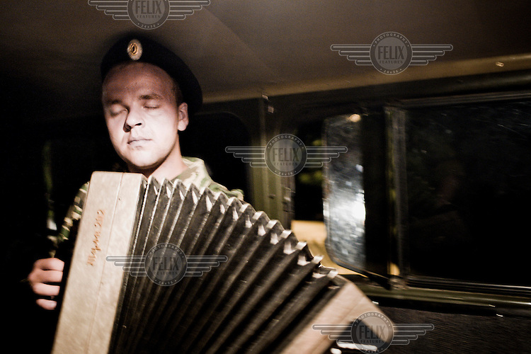 A Cossack soldier plays old army songs on an accordian in the back of a truck.