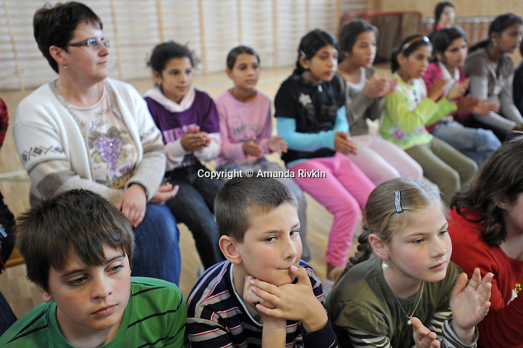 """Schoolchildren watch a performance of the play """"Dwarf"""" by the Roma or gypsy theater Romathan at the Banske Elementary School with a Roma or gypsy majority student body in Banske, Slovakia on June 2, 2010."""
