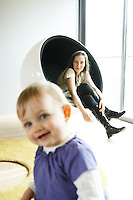 In the living room Helene relaxes in a 'Ball' chair by Eero Aarnio whilst in the foreground baby Alix smiles at the camera