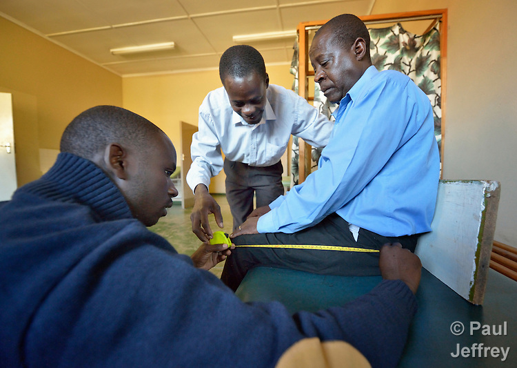 Wilson Bopoto (left) and Lucky Chirambaterere (center), technicians at the National Rehabilitation Centre in Ruwa, Zimbabwe, measure Sunny Nyamandwe for a wheelchair. The Centre assembles and fits wheelchairs provided by the Jairos Jiri Association with support from CBM-US.