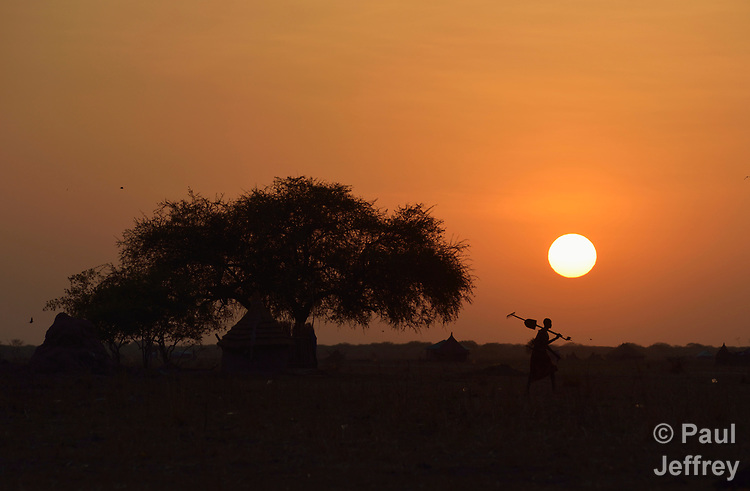 A farmer walks to his field as the sun rises in Dong Boma, a Dinka village in South Sudan's Jonglei State, on April 12, 2017. Most of the villagers here recently returned home after being displaced by rebel soldiers in December, 2013. They face serious challenges in reestablishing village life. The Lutheran World Federation, a member of the ACT Alliance, is providing support for housing, livelihood, and food security.