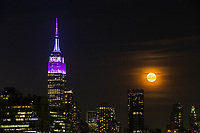 HOBOKEN, NJ - APRIL 11: The Empire State Building lit purple and gray in honor of the 100th anniversary of the New York state police while the moon rise over middle Manhattan as it is seen from the shore on April 11, 2017 in Hoboken, New Jersey. Since April 11, 1917, the State Police have been committed to helping New Yorkers by providing them with friendly, professional service. Photo by VIEWpress/Eduardo MunozAlvarez