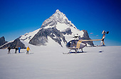 Tourists walk on the Tutoko glacier after a short helicopter flight from Milford Sound. Mount tutoko is in the distance, Fiordland National Park, South Island, New Zealand.