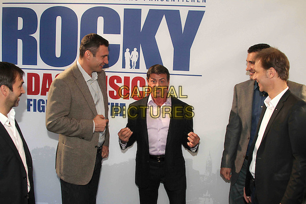 Michael Hildebrandt, Vitali Klitschko, Sylvester Stallone, Wladimir Klitschko, Johannes Mock O'Hara, Sylvester Stallone .Photocall for the musical 'Rocky' at stage entertainment headquarter, Hamburg, Germany. .November 20th, 2011.half length hand fist arms blue black grey gray pink shirt side profile facial hair.CAP/PPG.©People Picture/Capital Pictures