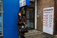 ROMANIA / Bucharest / 16.02.09..A woman leaves an exchange office in the posh Dorobanti neighborhod in northern Bucharest. Romania, which had the fastest-growing economy in the EU in the third quarter of last year, predicts a sharp slowdown this year that will lower budget revenue. The IMF said this month that the country probably faces a recession in 2009...© Davin Ellicson / Anzenberger